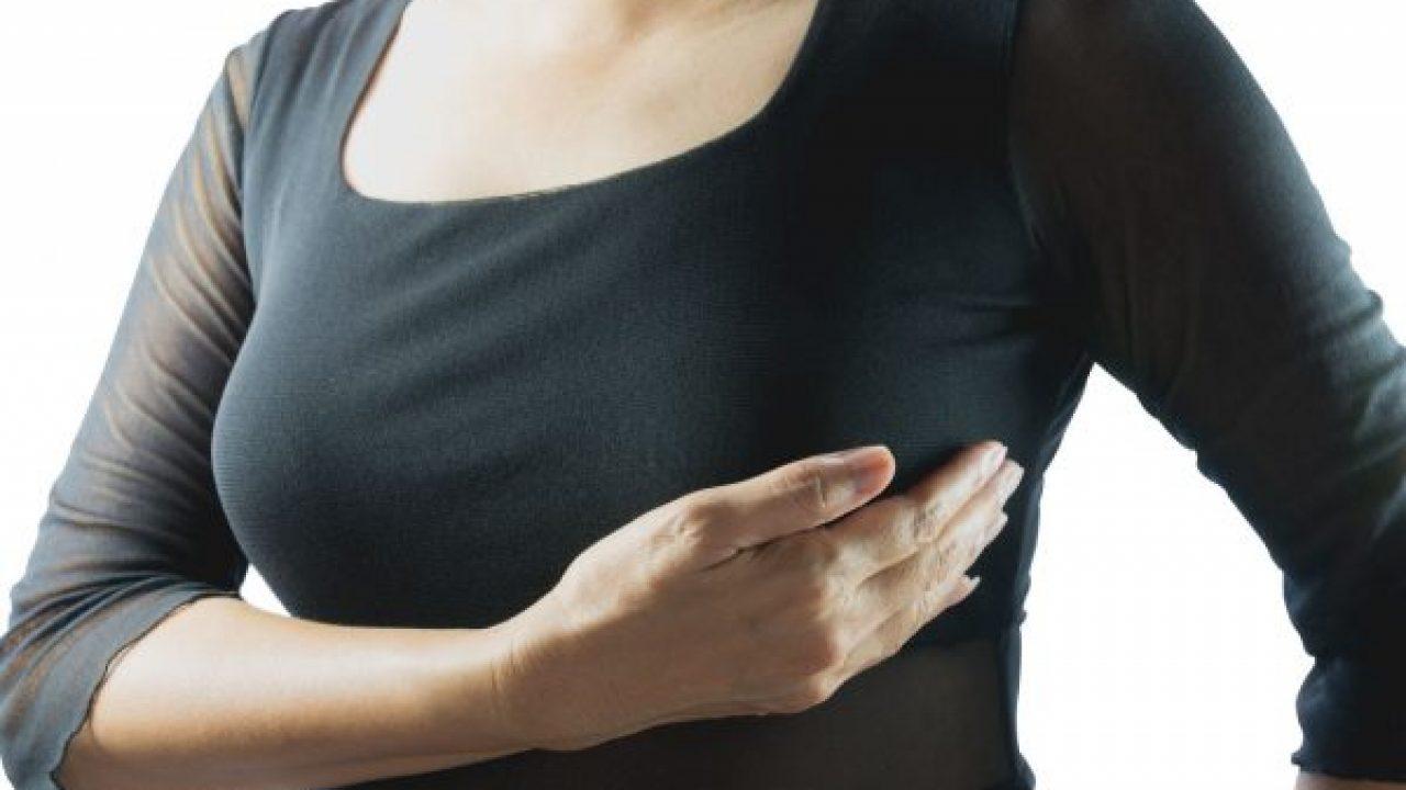 mulher com mãos em mamas sobre a blusa